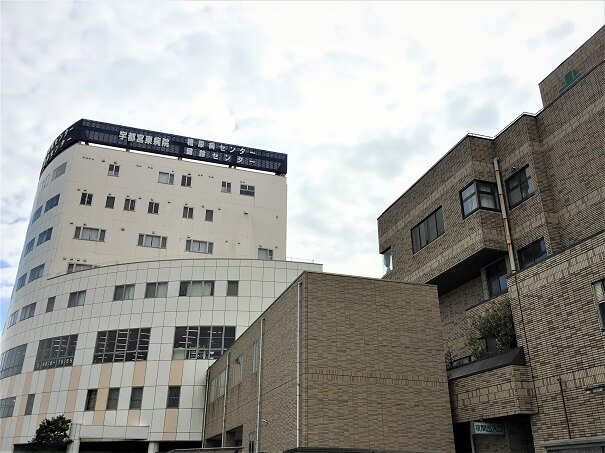 宇都宮東病院 外観 レンガ造りの病院本館とベージュ色、奥側は糖尿病/健診センター