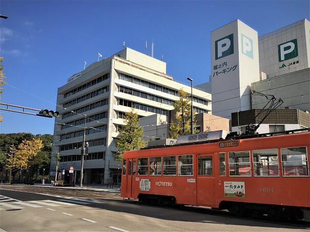 目の前は、伊予鉄道 南堀端駅、オレンジカラーの車両が鮮やか